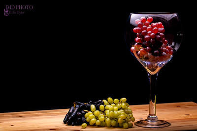 Winemaking. Glass of red wine grapes with green and black bunches. Black background with copy space.
