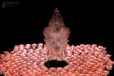 Spiritual enlightenment. Traditional buddha head statue illuminated by candles.