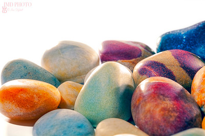 Assortment of tumbled beach pebbles studio shot against white background