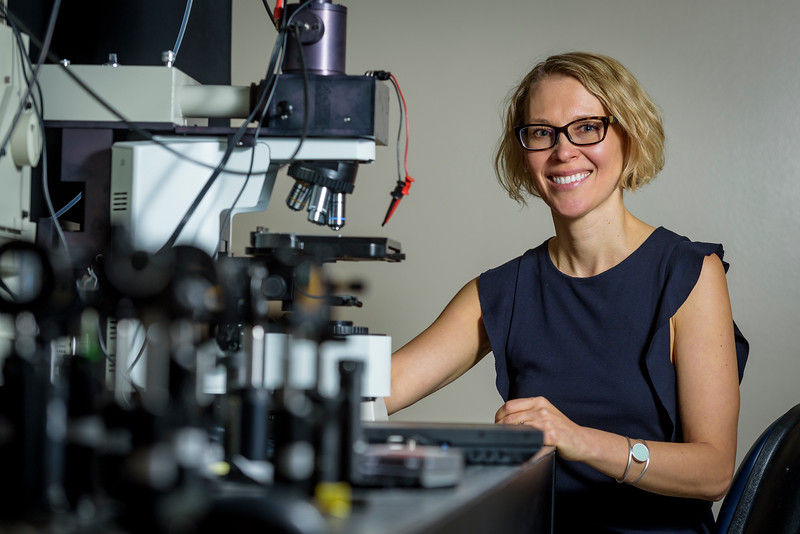 "Alexandra ""Sasha"" Boltasseva, Professor of Electrical and Computer Engineering, poses in front of a microscope within a nanophotonics lab at Birck Nanotechnology Center. (Purdue University photo/Alex Kumar)"