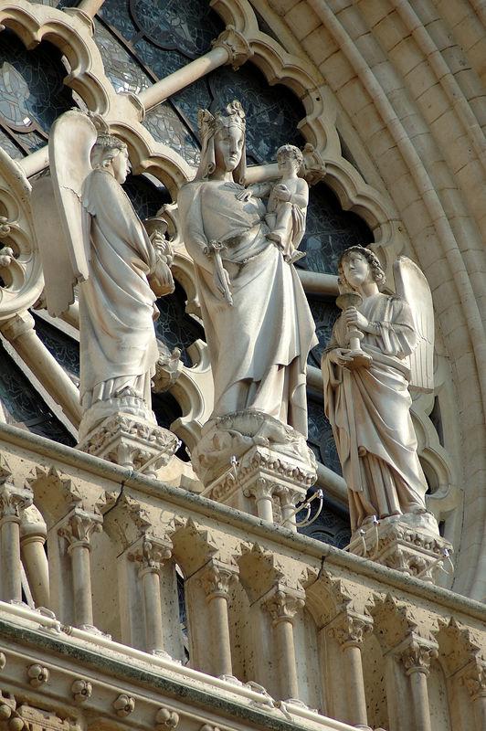 La Vierge portant l'enfant (dŽtail de la faade de notre damme de Paris). Elle est entourŽe de deux anges.<br /> <br /> Photo prise depuis le c™tŽ gauche du parvis.