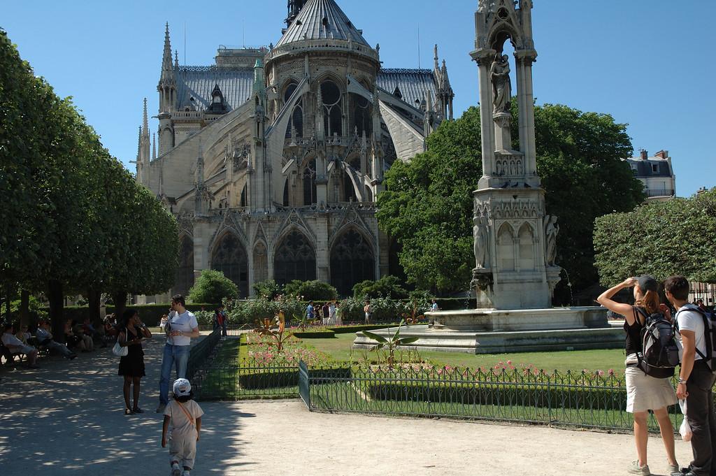 L'arrire de Notre Damme de Paris avec le petit jardin <br /> Avec des gens dans les premiers plans.