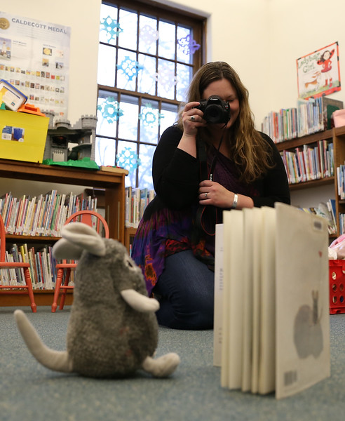 HOLLY PELCZYNSKI - BENNINGTON BANNER Katrina Hastings,<br /> Children's Librarian at The John G. McCullough Free Library photographs a stuffed animal during a stuffed animal sleepover event . Children leave their stuffed animals at during open hours on Friday and pick them up the next morning at Powers Market.