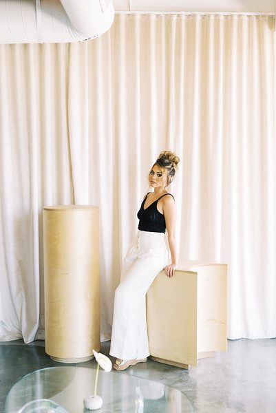 casual messy bun updo for long hair - RUBY FINCH - Las Vegas hair and makeup artists - KRISTEN KAY PHOTOGRAPHY - Las Vegas Elopement Photographer - Black knit top with white high-waisted pants #messybun #smokeyeye #editorial #hairstyle #fashion