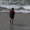 Hiker-wading-in-surf,-Sanders-Island,-Falkland-Islands