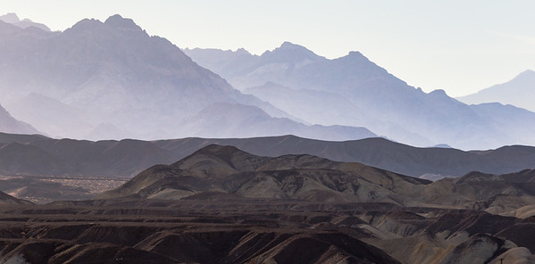 Layers of mountains and hills are seen from the bottom of Death Valley National Park in California