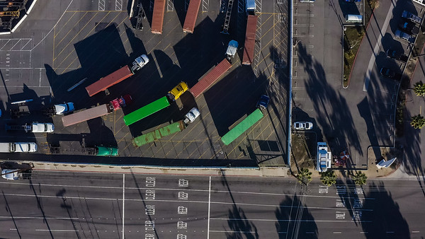 Aerial view of shipping container trucks entering port area before unloading to a container ship - San Pedro, Los Angeles, California, United States (US)