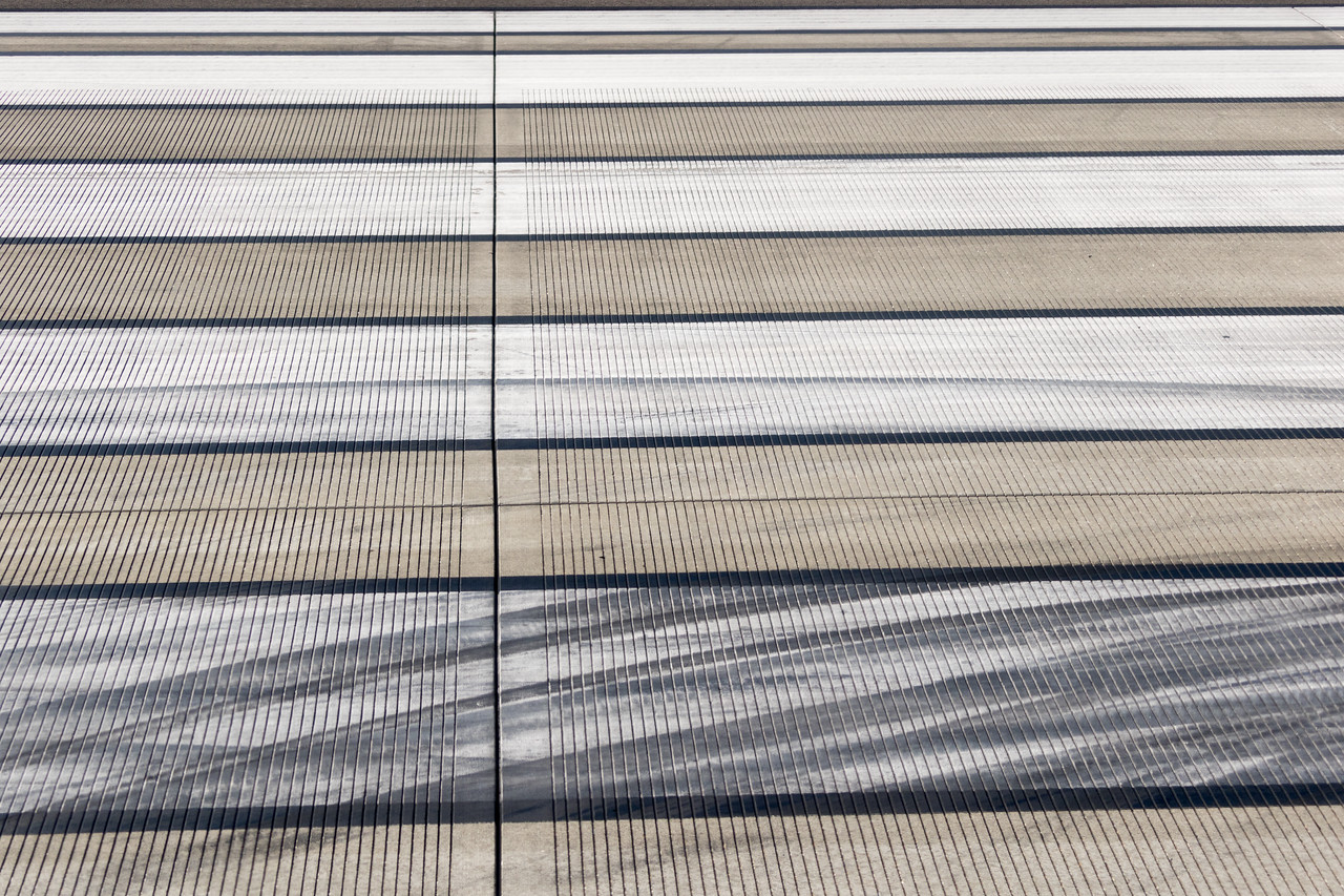 The landing stripes at an airport with skid tire tracks all over them.