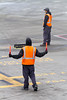 An airport work directs an incoming airplane to its parking location while another worker holds wheel chocks.