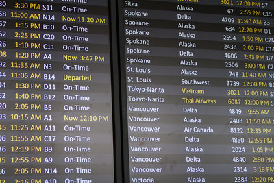 An airport flight board at SeaTac Airport shows current flight status and delays