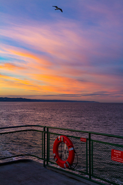 Clouds catch various shades of wonderful colors after sunset as seen from a Washington State Ferry crossing from Whidbey Island to Mukilteo, Washington