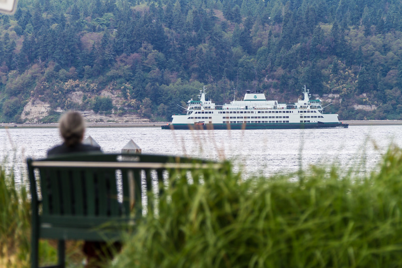 Woman sitting on bench and passenger ferry in background - USA - Washington