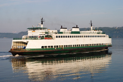 The Washington State Ferry Sealth crosses Puget Sound with the Olympic Mountains in the background.