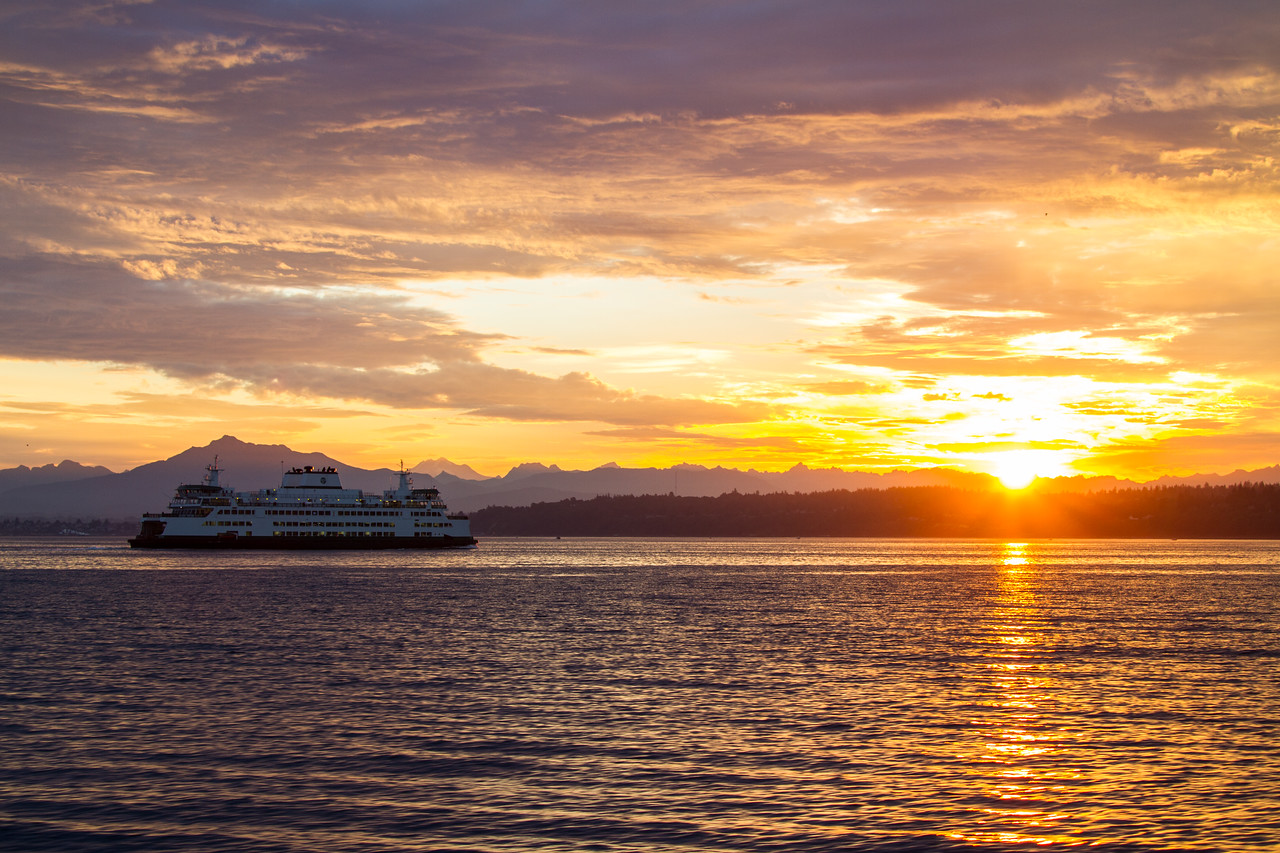 Washington State Ferry Tokitae crossing in front of sunrise over the Cascade Mountains- USA - Washington