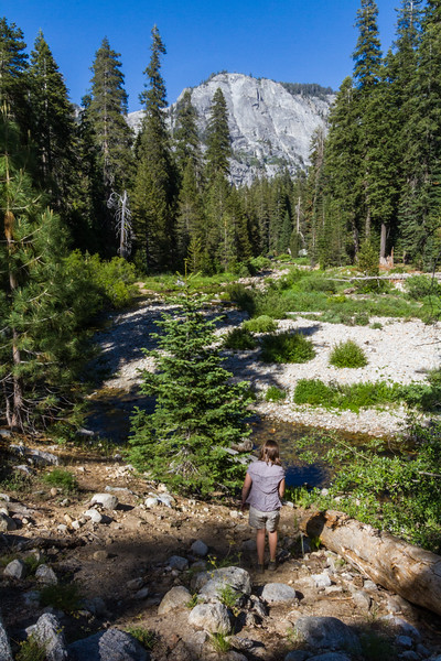 A young girl looks over a small river and distant granite  peaks in Sequoia National Park, California.