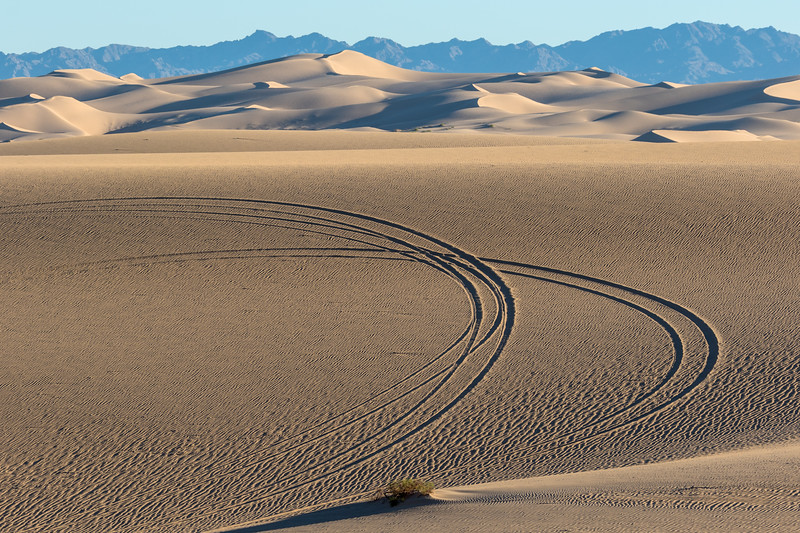 ATV tracks left in perfect sand formations in front of the Chocolate Mountains of California