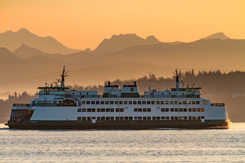 The M/V Kittitas crosses in front of the Cascade Mountains as the sun rises in Washington.