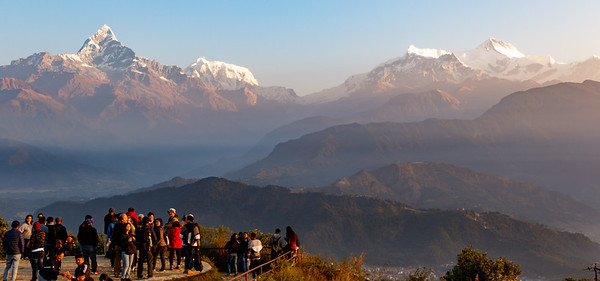 Tourists watch the sunrise light up the Machapuchare and the Himalayas from Sarangkot, Pokhara, Nepal