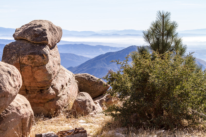 View overlooking San Bernadino Valley and mountain range with rocks and trees in foreground - California - USA