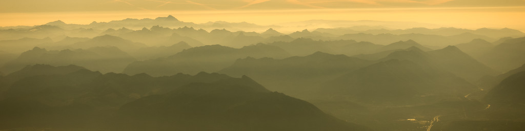 Mountains in California at sunset are seen in progressing layers toward the horizon in an aerial photo