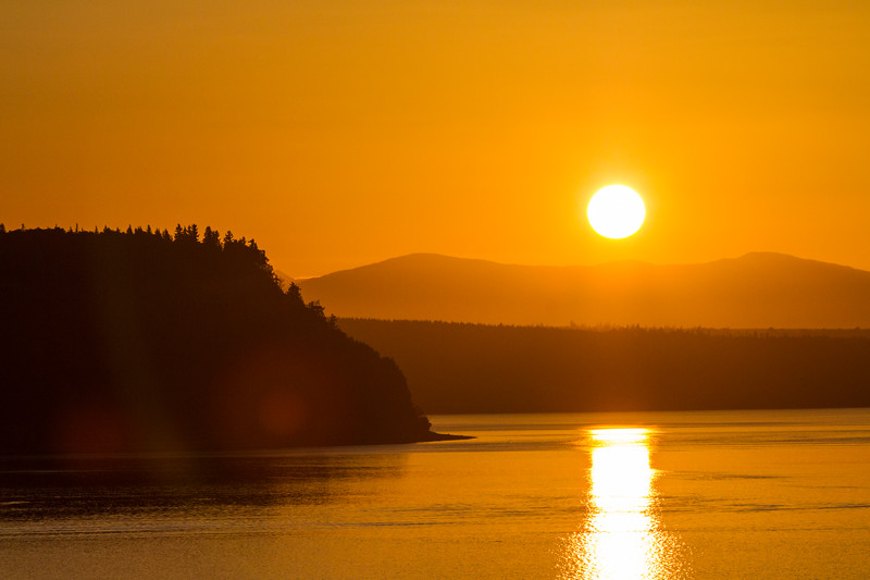 The golden sun rises over teh Cascade Mountains and Camano Island in Puget Sound, Washington, as seen from Langley, Whidbey Island