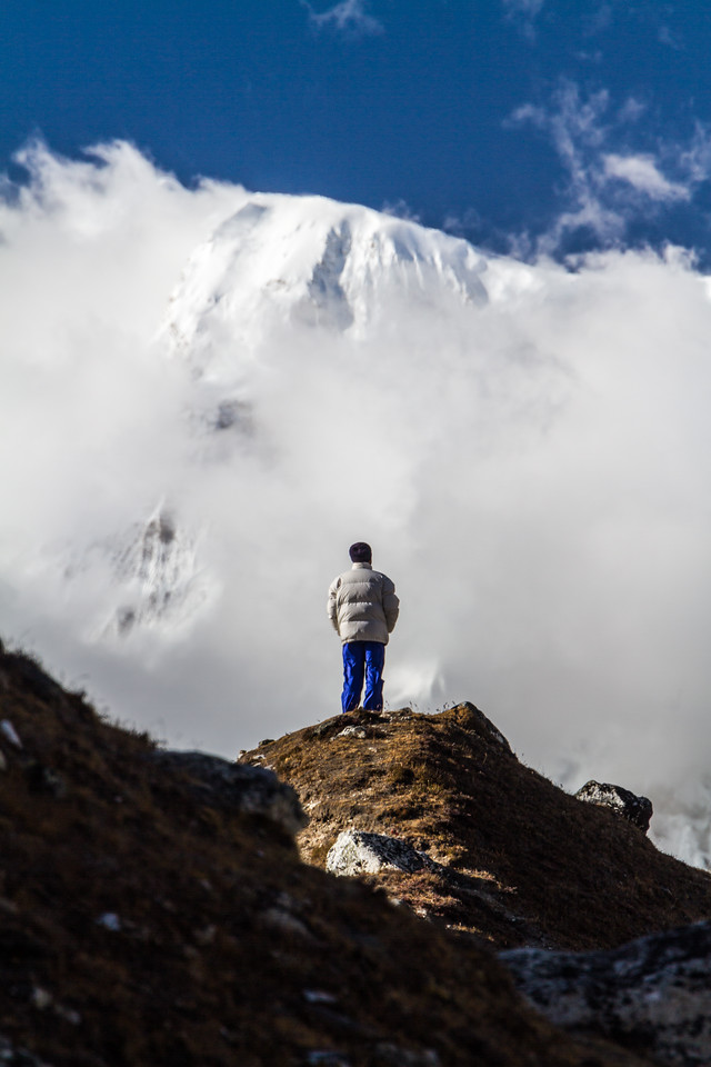 Man standing on rock and snowcapped mountain in background - Nepal