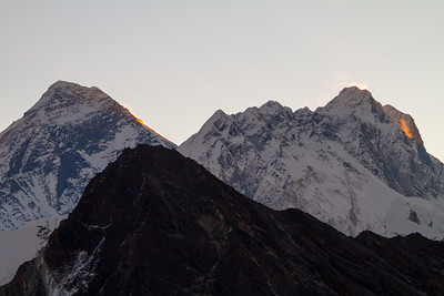 Mount Everest and Nuptse are seen at sunrise, backlit by the sun with golden spindrift on their flanks. Gokyo Ri, Khumbu, Nepal.