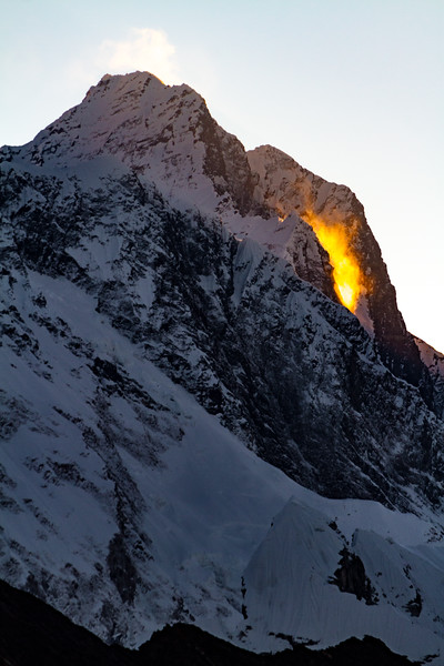 Spin drift off teh side of a Himalayan peak catches the golden light of sunrise against an icy, mountain