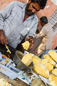 Man weighing jaggery in market - India