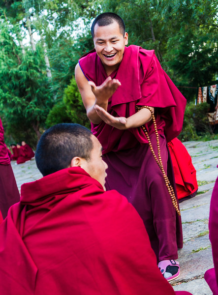 Bhutanese Buddhist monks engage in philosophical debates in the courtyard of a monastery in Bumthang, Bhutan