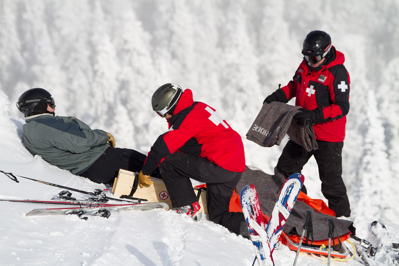 Two ski patrol technicians attend to an injured skier on the side of a ski resorts
