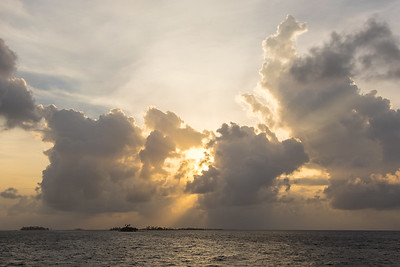 Tropical clouds at sunrise hide a rising sun with orange overtones above the Caribbean Sea in Panama