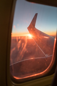 Sunset out a commercial airline window with the wing visible
