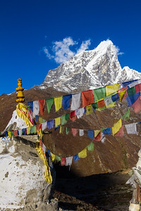 Sherpa prayer flags, attached to a Buddhist stupa (chorten) fly in teh weind in front of distant snowy peaks - Dingboche - Solukhumbu - Nepal