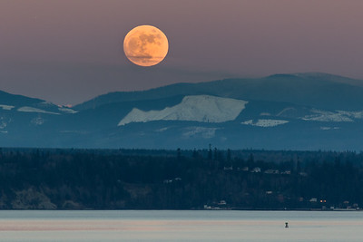 The full, golden moon rises above the Cascade Mountains of Washington state with Puget Sound in the foreground.