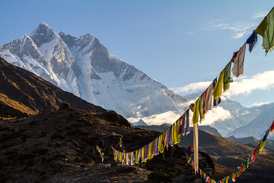 Buddhist prayer flags fly in front of distant snowcapped mountains in the Solukhumbu Region of the Nepali Himalayas - Dingboche - Nepal