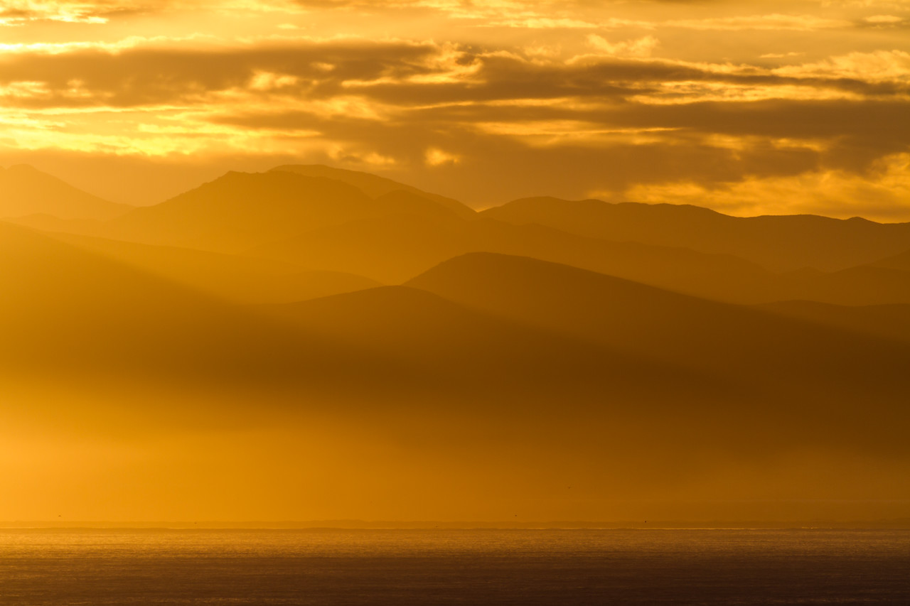View of sunrise at sea with mountains in background