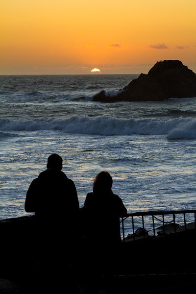 Silhouette of couple standing near seaside at sunset