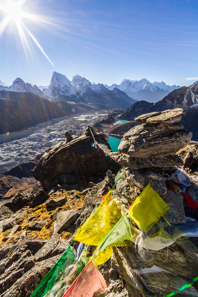 Prayer Flags And Rock Cairn Above Glacier And Valley In Himalayas With Sun, Gokyo Ri, Nepal, Asia