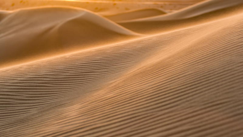Bright evening sun captures the spindrift off sand dunes at Algodones Dunes in california