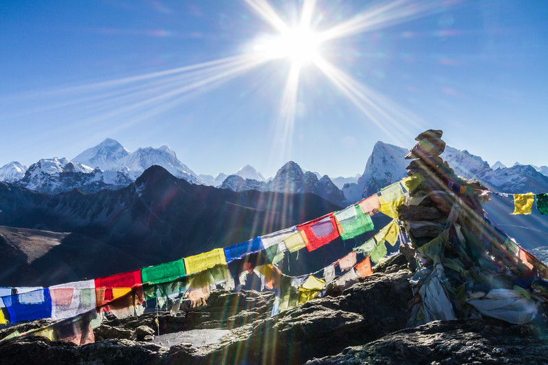 The Sun Hovers Above A Rock Cairn Adorned With Prayer Flags With Mount Everest In The Background, Gokyo Ri, Himalayas, Nepal