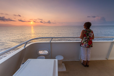 Woman standing in cruise ship and looking at sunrise - USA - Hawaii - Maui