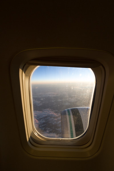 Clouds are lit by the setting sun as seen from the inside of a commercial airplane window at high altitude