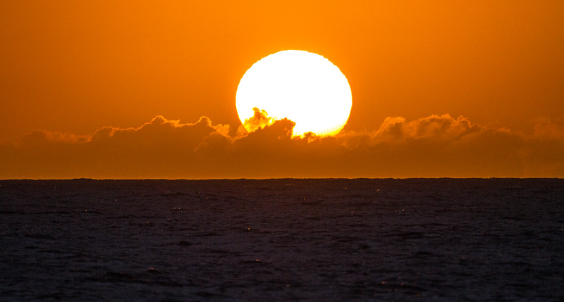 The sun sets over a small bank of clouds above the Pacific Ocean off the shore of Hawaii