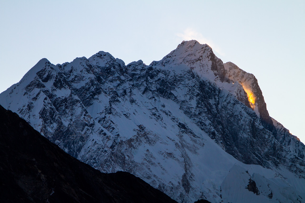 Sun lights a snow drift at sunrise along the flank of a Himalayan peak