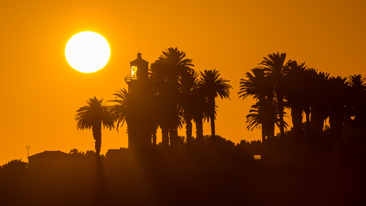 The sun sets behind Point Vicente Lighthouse as a golden ball in perfect orange sky - California Coast