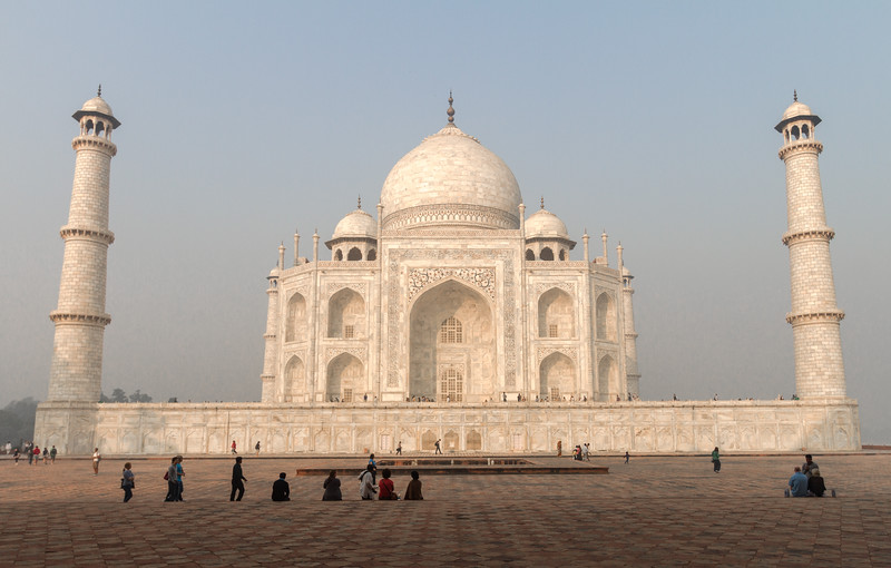 Tourists sit on the steps in front of the Jawab and admire the Taj Mahal in morning light just after sunrise.