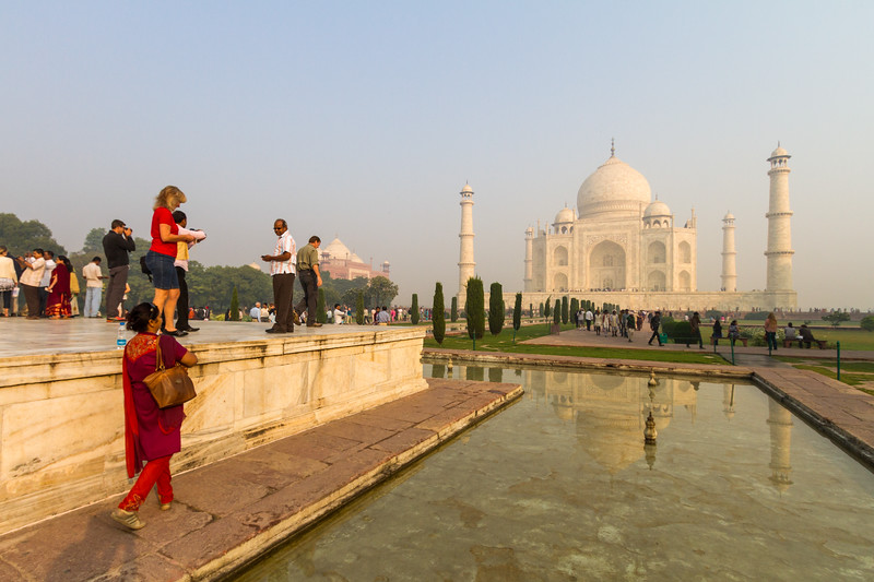 Tourists stand on the dais next to a reflecting pool in front of the Taj Mahal to take photographs.