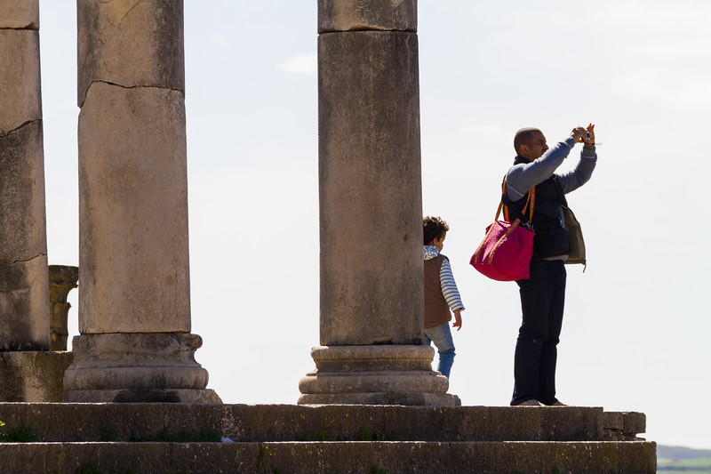 Tourist photographing at Ruins of Volubilis lie scattered in the Moroccan countryside - Morocco - Volubilis