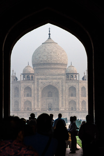 Tourists pile through the arch openings that lead to the Taj Mahal, which can be seen framed in one arch.